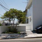 駐車スペースの脇にある小さな植栽がエントランスを彩る (山手町の家)